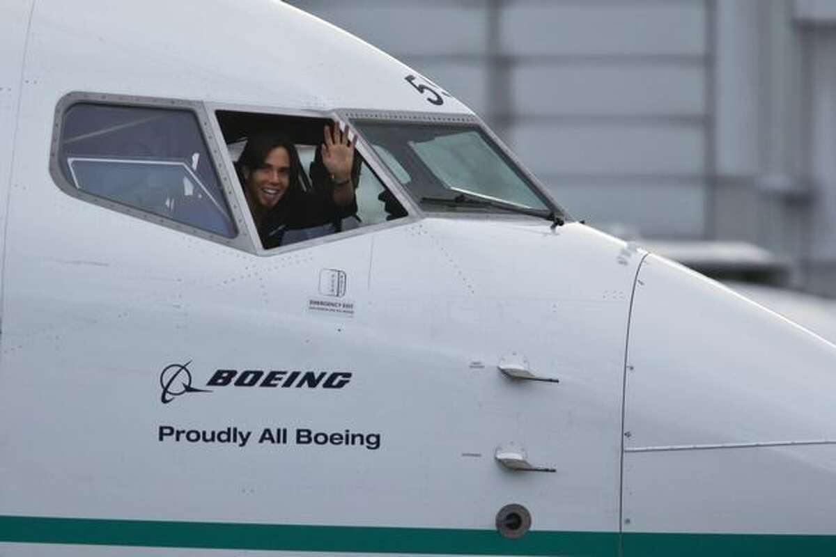 Olympic gold medalist Apolo Ohno waves from the cockpit of the Boeing 737-800 that has been painted with his likeness.