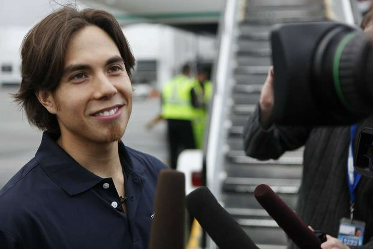 Apolo Ohno meets with the media outside the Alaska Airlines 737-800 that bears his picture.