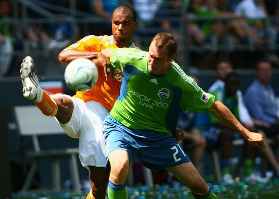 Nate Jaqua battles for the ball with a Houston Dynamo defender in the second half. Photo: Daniel Berman/Seattlepi.com