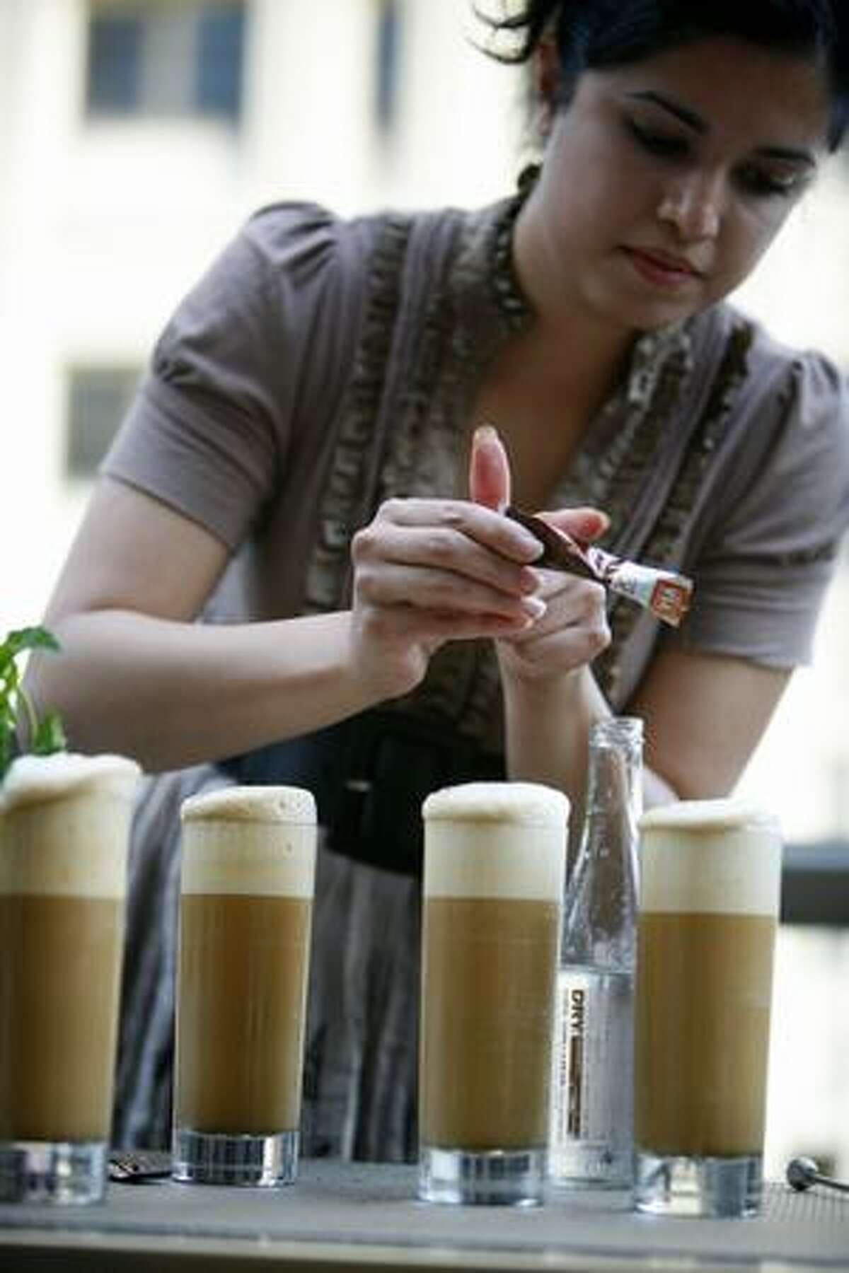 Anu Apte of Rob Roy in Belltown sprinkles Starbucks VIA Ready Brew coffee onto a drink during a bartender competition at Hotel 1000 where the drink makers used Starbucks VIA Ready Brew coffee.