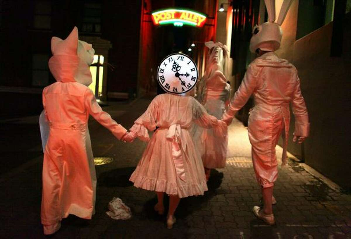 Performers in Lullaby Moon make their way along Post Alley while celebrating the new moon in the streets of downtown Seattle on Thursday.