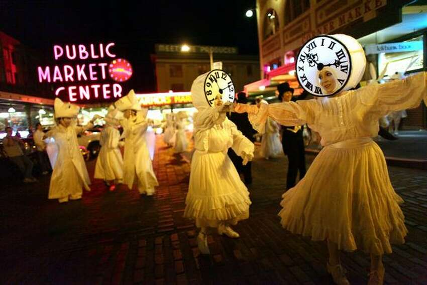 Performers in Lullaby Moon, a show celebrating the new moon, perform in front of Pike Place Market on Thursday.