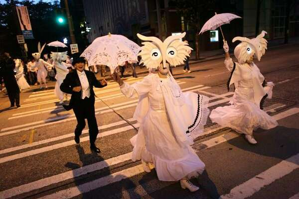 Performers in Lullaby Moon, a show celebrating the new moon, dance through downtown Seattle on Thursday.