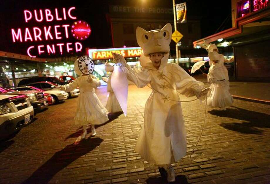 Performers in Lullaby Moon perform in front of Pike Place Market on Thursday. Photo: Joshua Trujillo, Seattlepi.com