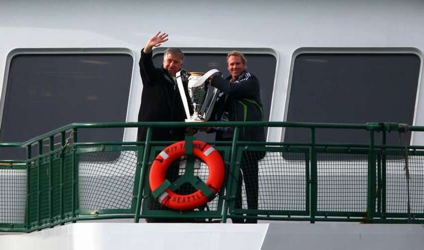 Seattle Sounders coach Sigi Schmid and former MLS Cup winner Chris Henderson accompany the Philip F. Anschultz MLS Cup trophy aboard the Washington State Ferry M/V Tacoma on Wednesday as they approach the Coleman Dock in Seattle. The arrival of the trophy kicked off events for Sunday's championship match at Qwest Field.