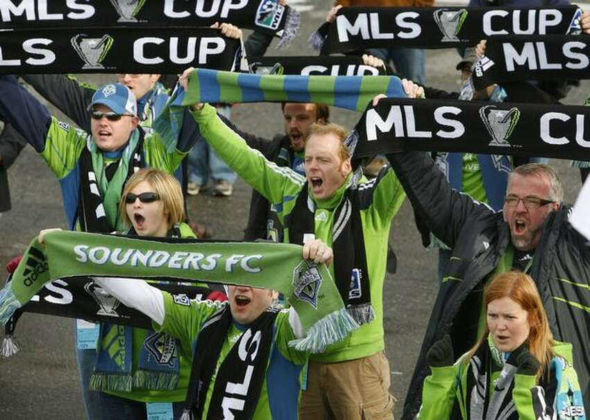 MLS fans cheer as the Philip F. Anschultz MLS Cup trophy arrives aboard the Washington State Ferry M/V Tacoma on Wednesday. The arrival of the trophy kicked off events for Sunday's championship match between Real Salt Lake and LA Galaxy at Qwest Field.