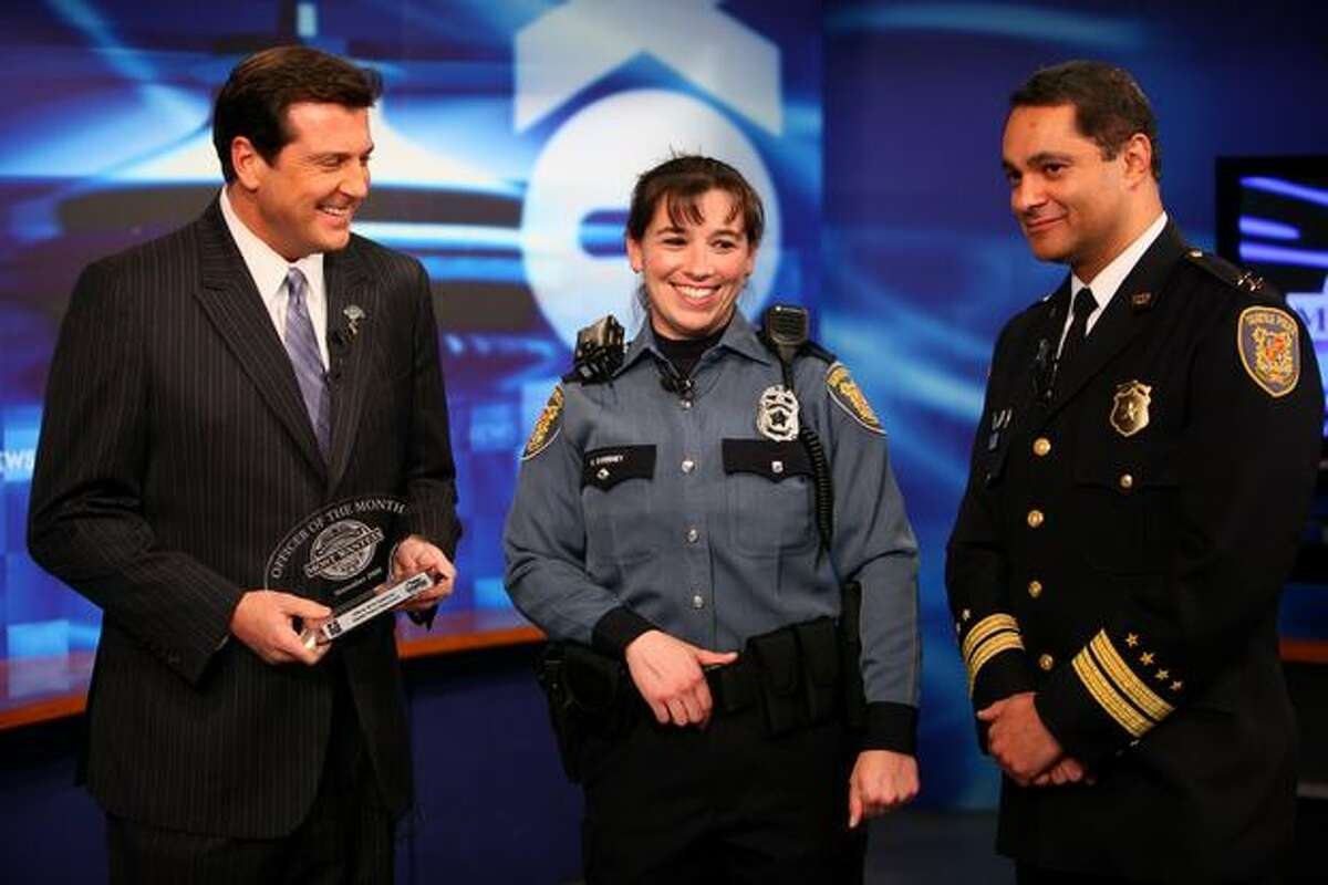 Seattle Police Officer Britt Sweeney is awarded Officer of the Month by Washington's Most Wanted host David Rose at the Q13 FOX studios in Seattle. Assistant Seattle Police Chief Nick Metz, right, said Sweeney, a rookie, reacted to the Halloween shooting death of her field training officer with the skill of a 10 year veteran of the force.
