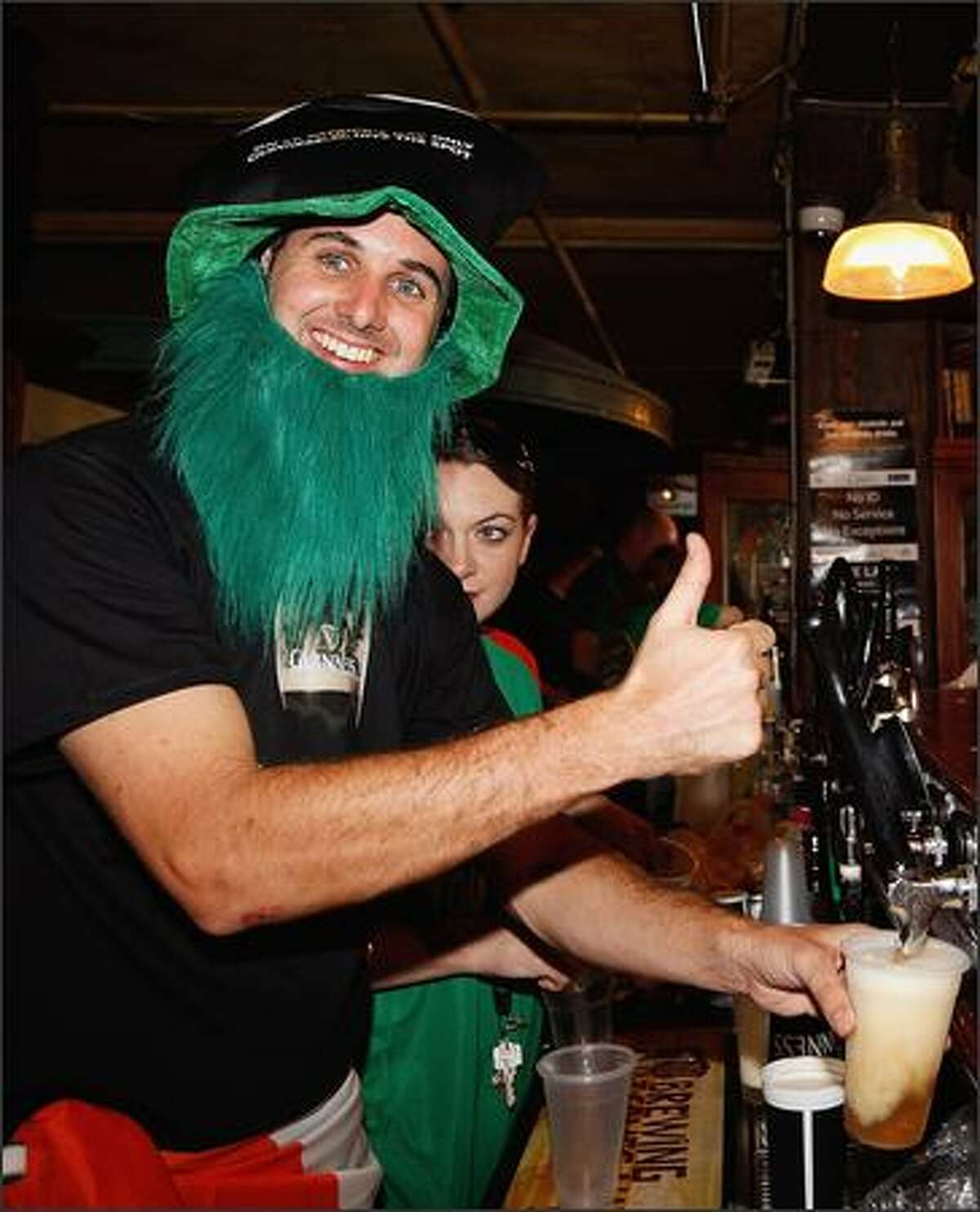 Connor Fidel pours pints of Guinness on St. Patrick's Day at the Muddy Farmer Bar in Auckland, New Zealand.
