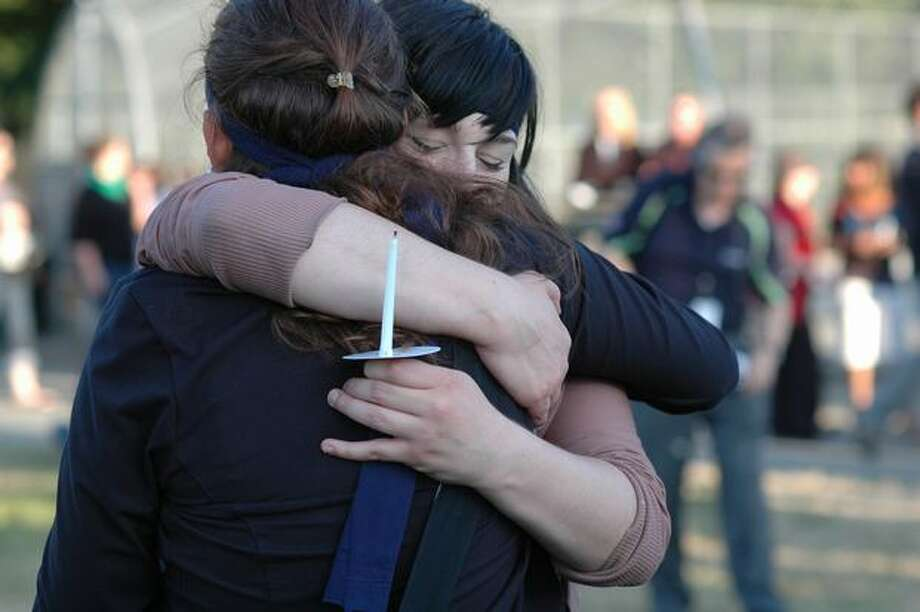 Amanda Wright hugs friend Bethanie Stallman at the start of a candlelight vigil for the victim of a stabbing early last week at the South Park Community Center. Photo: Daniel Berman/Seattlepi.com