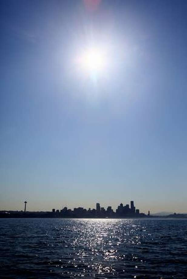 The sun beats down on Seattle on Monday, as seen from Elliott Bay. High temperatures have prompted heat warnings for the week. Photo: Joshua Trujillo/seattlepi.com