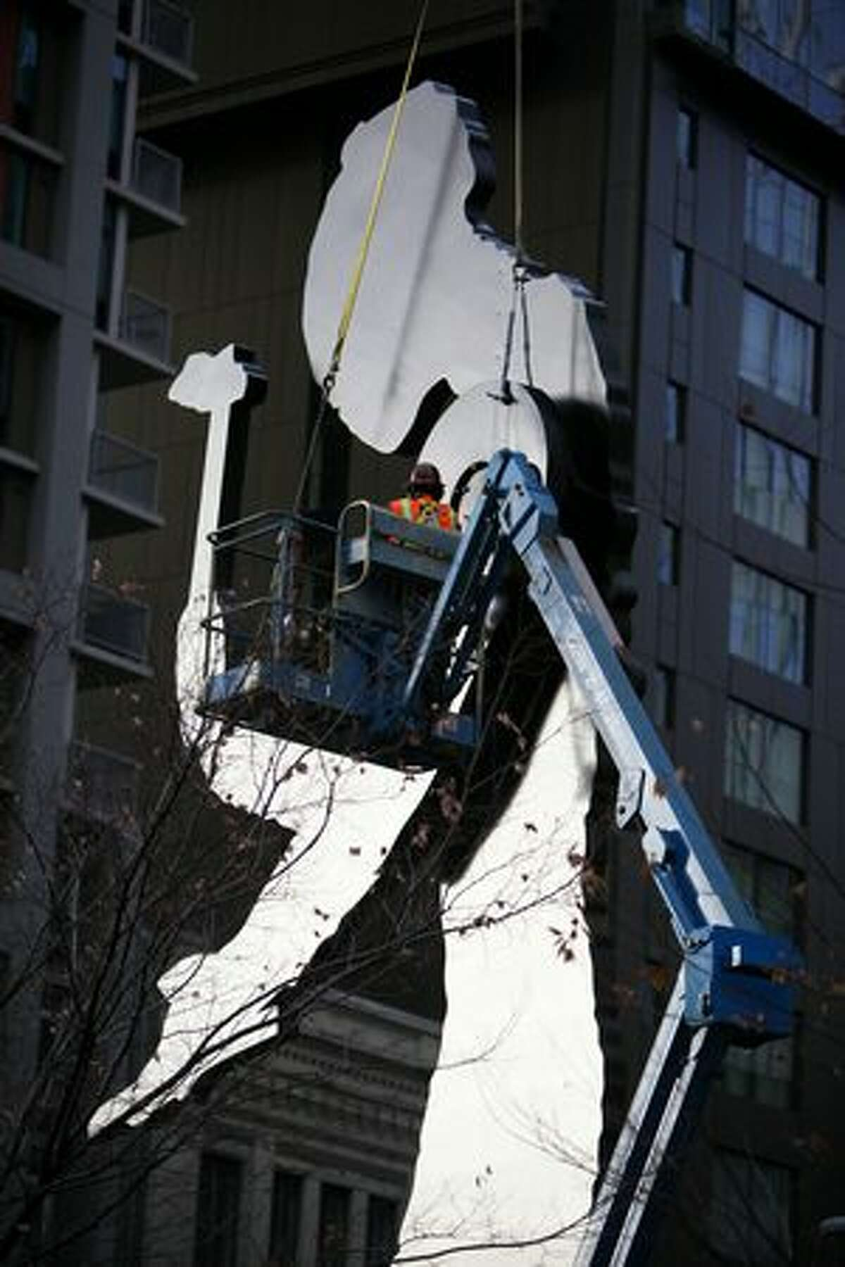 """Workers unbolt the hammer and arm from downtown Seattle's iconic """"Hammering Man"""" in front of the Seattle Art Museum. Since Hammering Man was installed in 1992 his hammer has logged nearly 90,000 hours, striking 4 times a minute, or roughly 21,600,000 strikes."""