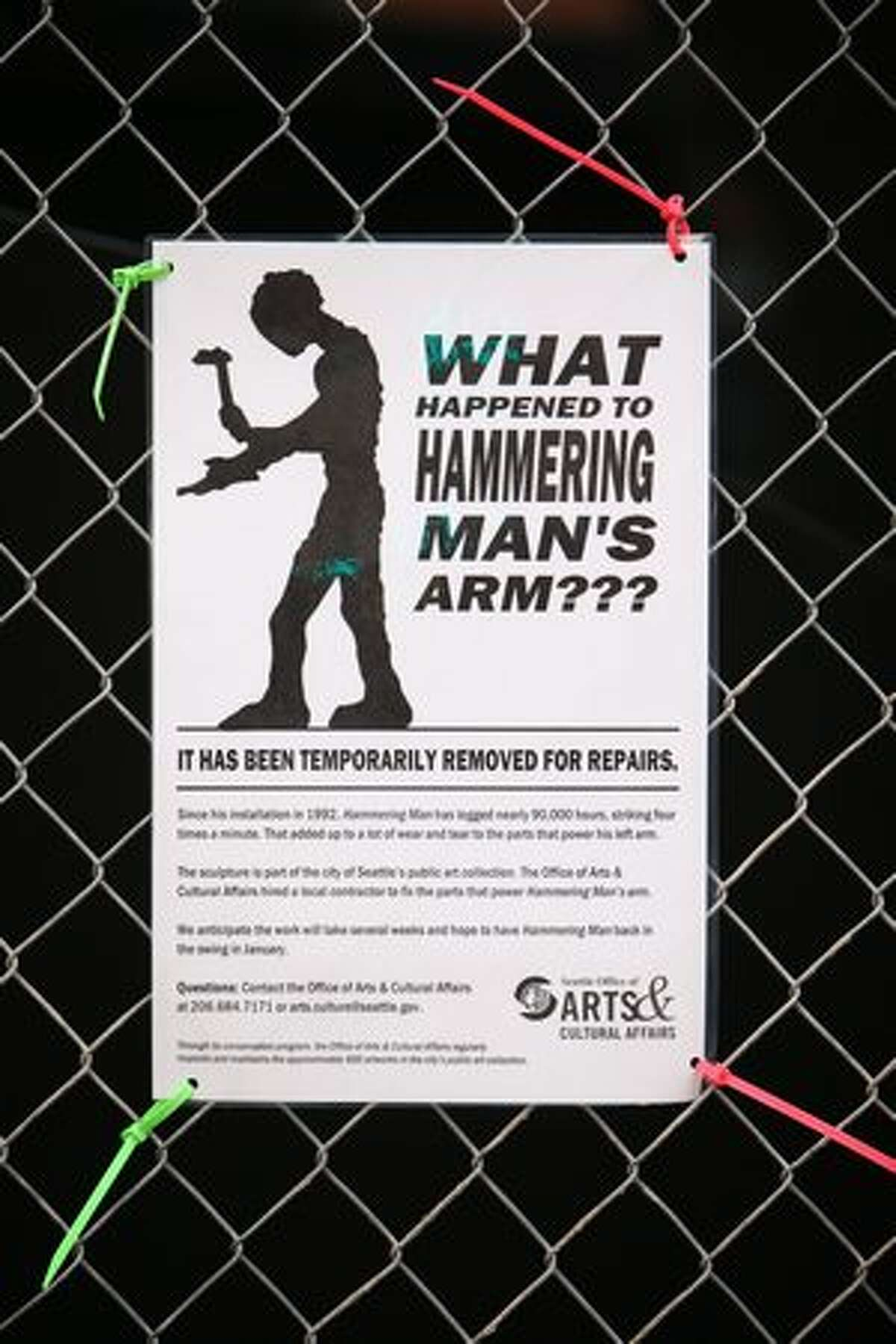 """A sign explains what happened to the arm on """"Hammering Man."""""""
