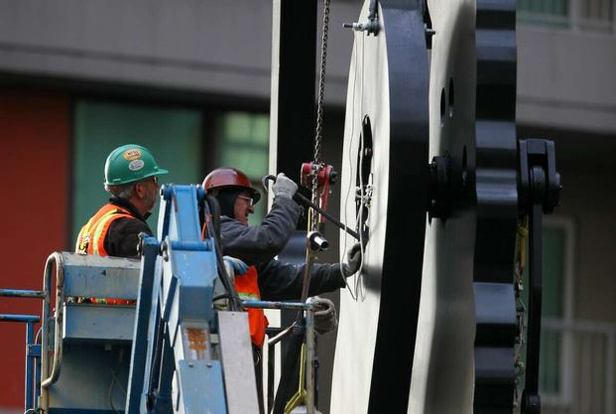 """Workers remove the hammer and arm from downtown Seattle's iconic """"Hammering Man"""" in front of the Seattle Art Museum on Tuesday November 24, 2009. Since Hammering Man was installed in 1992 his hammer has logged nearly 90,000 hours, striking 4 times a minute, or roughly 21,600,000 strikes."""