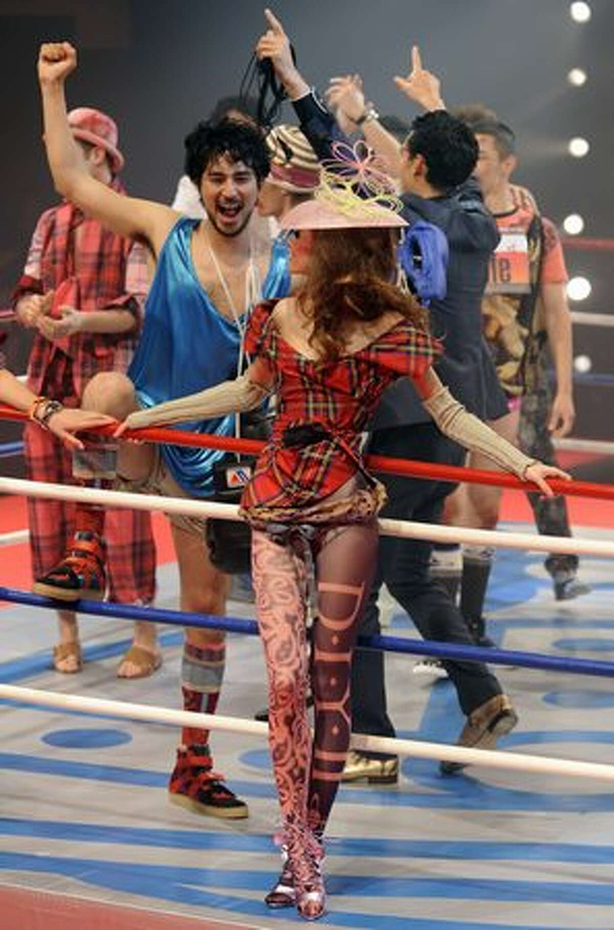 Models celebrate the finale of the fashion show of British designer Vivienne Westwood at a boxing stadium in Tokyo.