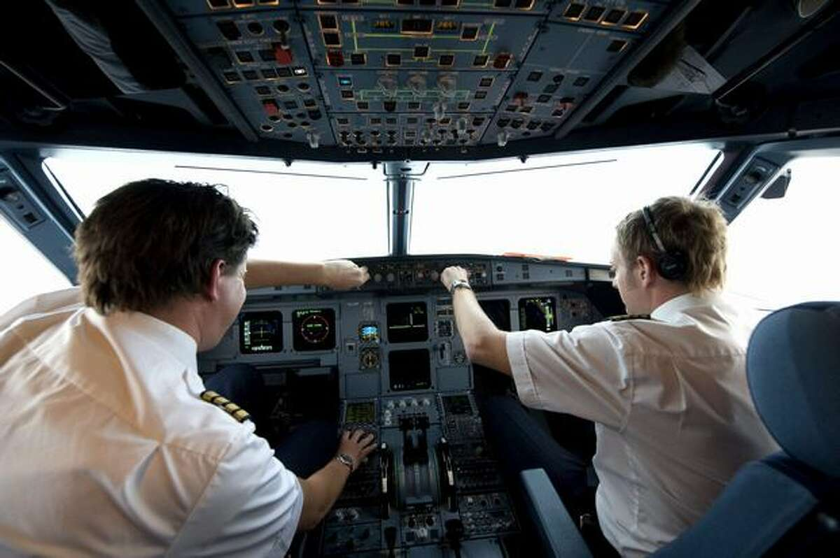 Pilots Henrik Ekstrand (left) and Andreas Liner of Novair Airline demonstrate a new approach technique flying an Airbus A321 to Arlanda airport in Stockholm, Sweden, on Nov., 25, 2009.(PONTUS LUNDAHL/AFP/Getty Images)
