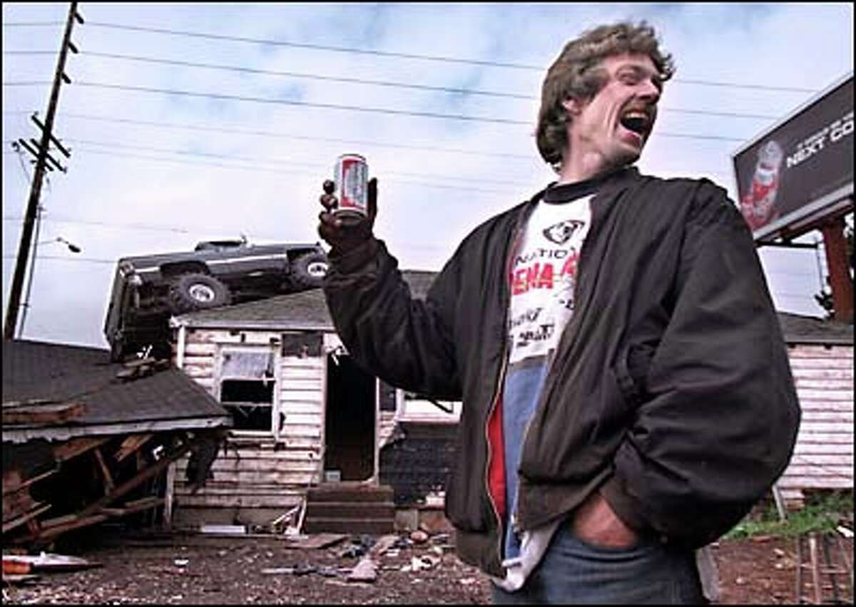 Dave Anthony toasts his achievement after driving his truck on top of a Kent house he was demolishing. Anthony said