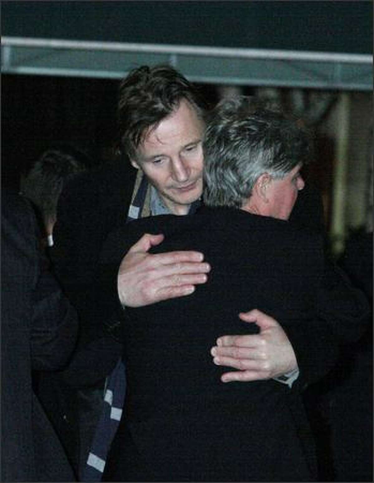 Liam Neeson, left, embraces an unidentified man after exiting the American Irish Historical Society where the body of Neeson's wife, Natasha Richardson, was lying in repose Friday, March 20, 2009 in New York. (AP Photo/Tina Fineberg)