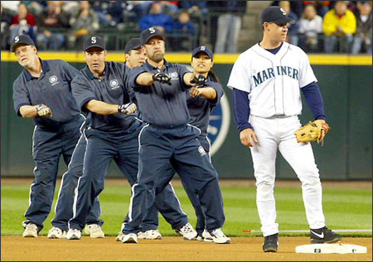 The Mariners' ground crew performs a dance routine behind second baseman Bret Boone between the third and fourth innings of a game against the Cleveland Indians.