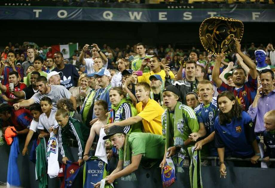 Sounders and Barcelona fans scramble to get the attention of the Barcelona players as they walk off the field. Photo: Joshua Trujillo/seattlepi.com