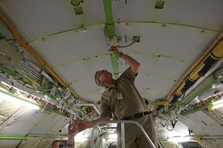 Boeing systems engineer Jeff Lawrence inspects electrical components onboard 787 on the production l