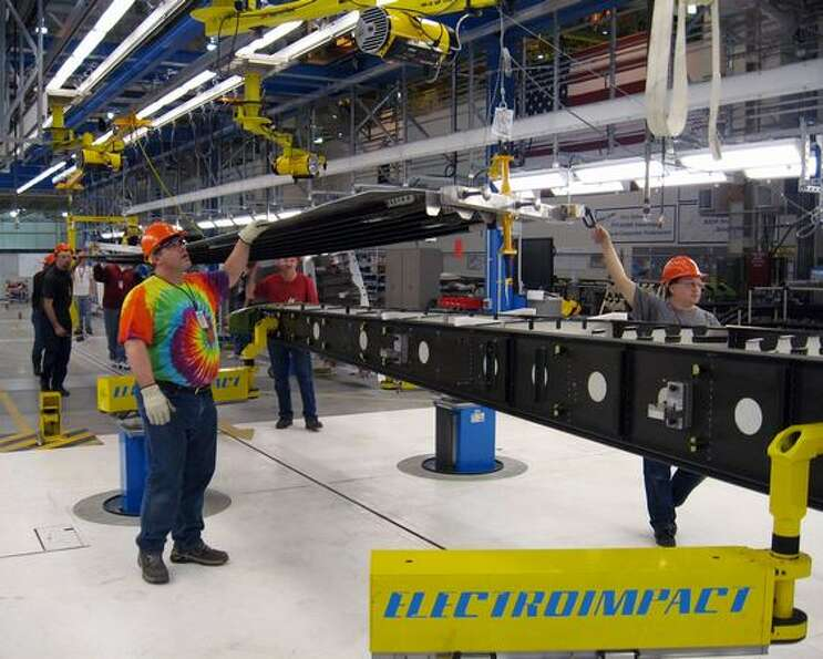 Employees at the Boeing Frederickson Composite Manufacturing Center transfer a skin panel sub-assemb