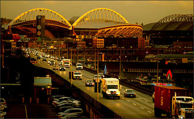 Traffic heads northbound on the Alaskan Way Viaduct at sunset, as the remaining light glows off Qwest Field in the background in this 2005 file photo. Photo: P-I File