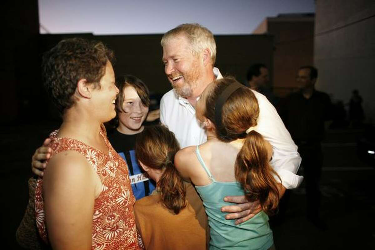Candidate for Seattle mayor Mike McGinn embraces his family (from left, wife Peggy Lynch, sons Jack, 14, and Cian, 9, and daughter Miyo, 12) during a campaign party in Capitol Hill on Tuesday night after the first release of results showed McGinn leading.