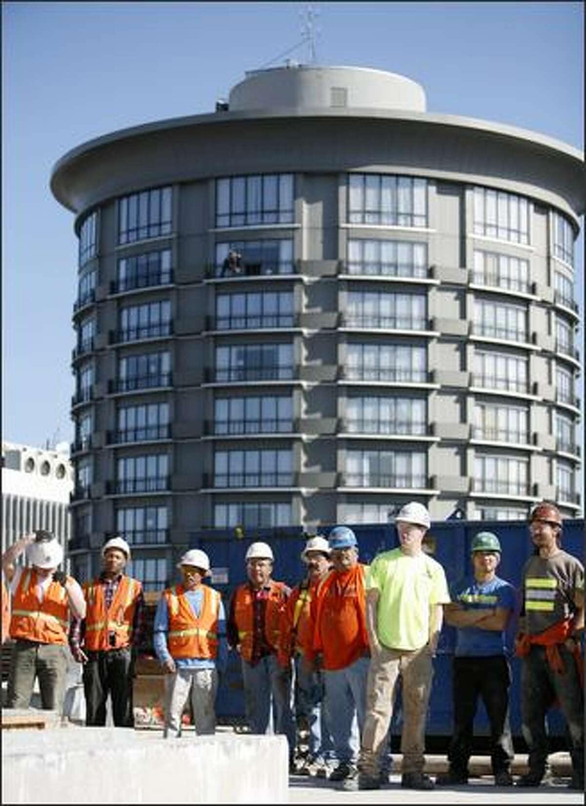 Construction workers participate in a ceremony on the roof of the Escala building.