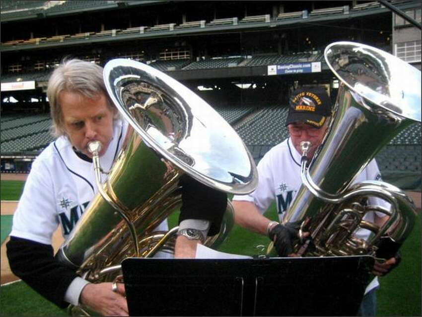 Tuba players Mark Lloyd, left, and Michael Russell, retired principal tuba player for the Seattle Symphony Orchestra, practice for their performance Tuesday at the Mariners home opener.