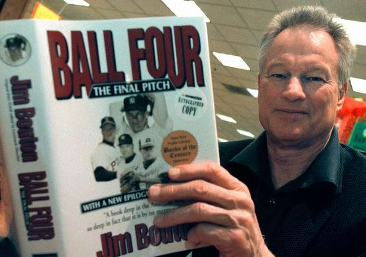 """Former Seattle Pilots pitcher Jim Bouton signs copies of his book """"Ball Four: The Final Pitch"""" in this November 2000 file photo. (Photo by Tim Boyle/Newsmakers)"""