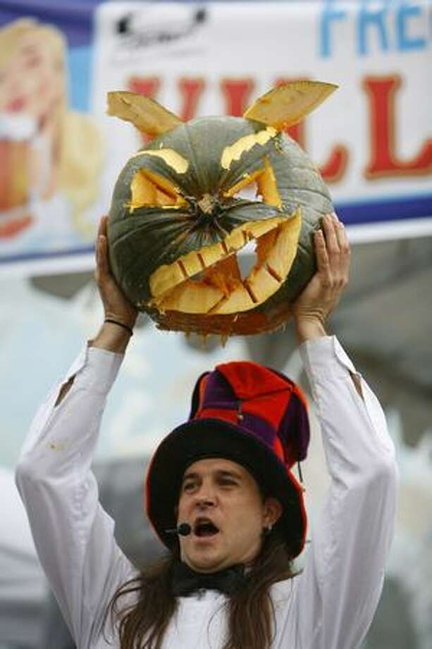 David Roman raises the winning pumpkin during theTexas Chainsaw Carvin' competition at the Fremont's Oktoberfest celebration on September 19, 2009 in Fremont. Photo: Joshua Trujillo, Seattlepi.com