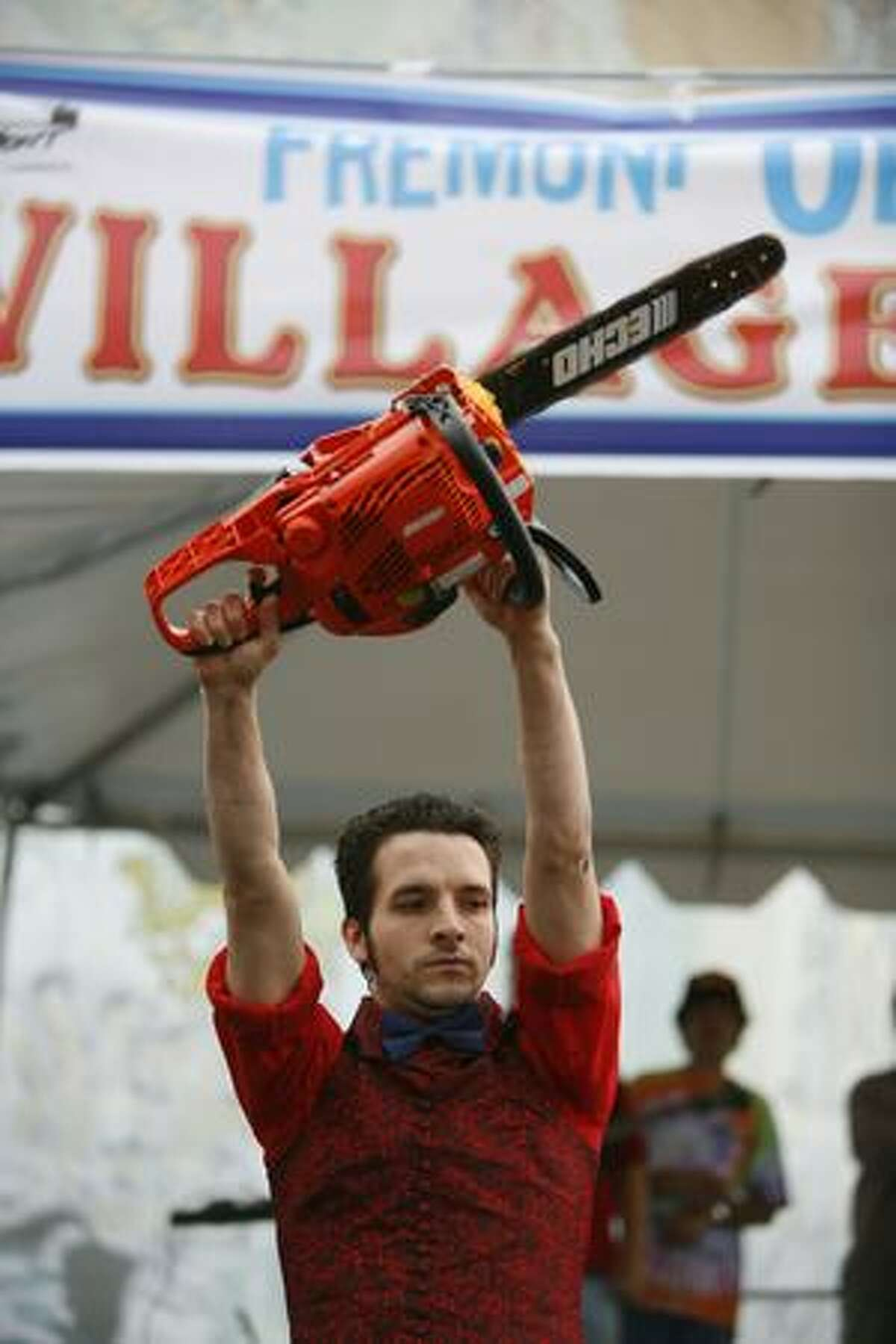 Ian Stone raises his chainsaw during the Texas Chainsaw Carvin' competition during Fremont's Oktoberfest celebration on September 19, 2009 in Fremont.
