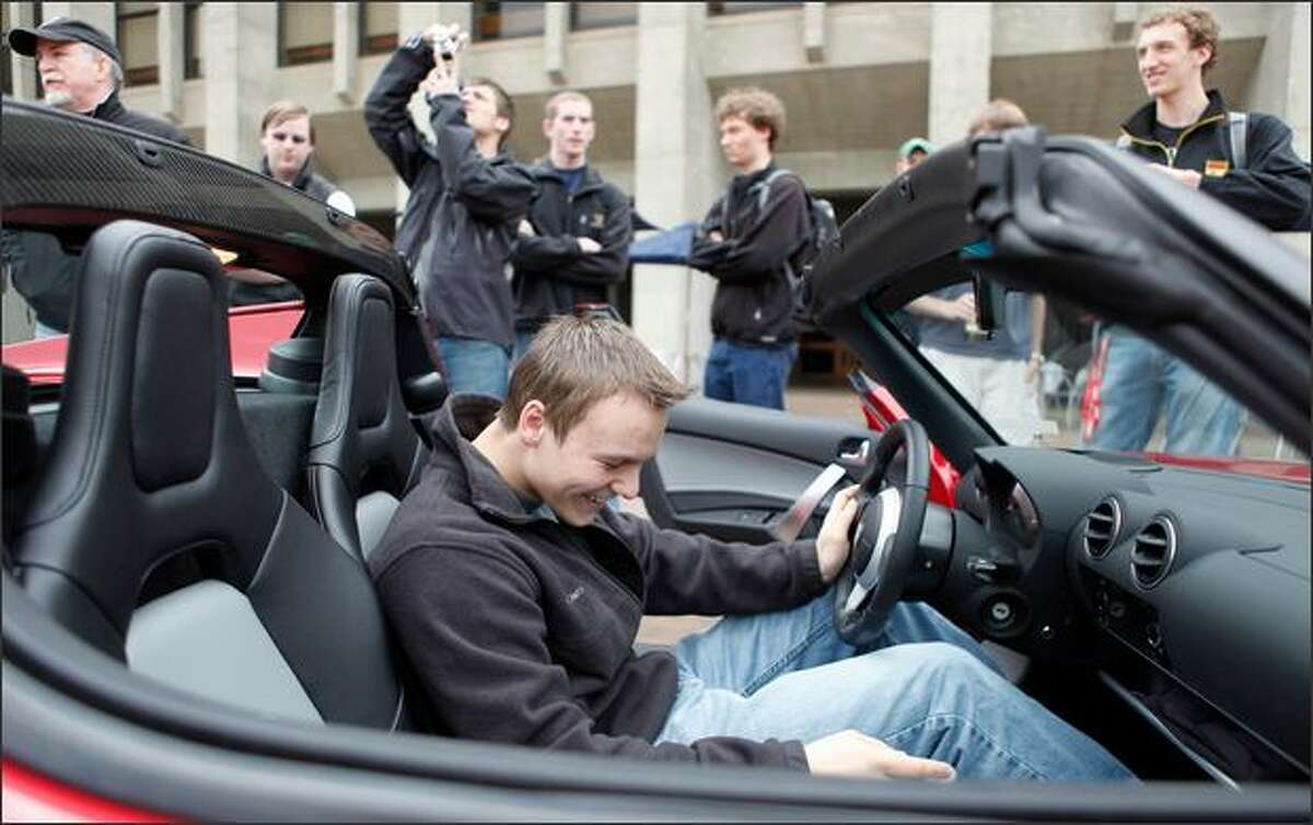 Student David Frolov sits in a Tesla battery-operated car at an electric car show in Red Square on the University of Washington campus.