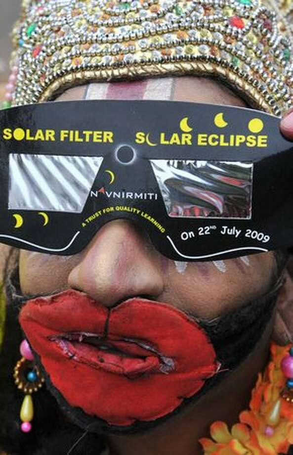 Indian artist B. Nookaji, dressed as Hindu ape god Hanuman, uses sunglasses to watch the solar eclipse in Hyderabad, India. The annual event is India's longest lasting solar eclipse of the last millenium which will remain at its peak 11 minutes and travel from southern India's Tamil Nadu state to the northeast of the country. Photo: Getty Images