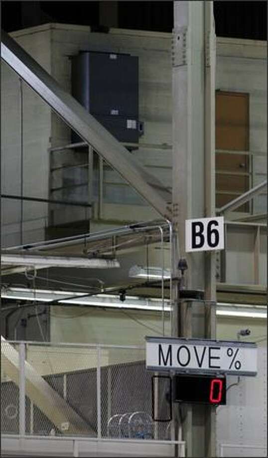 Electronic signs are displayed to help workers and management identify and fix problems along the assembly line. This sign's 0 percent move indicates that no planes have moved forward on the assembly line by that point in the day. Photo: Clifford DesPeaux, Seattlepi.com