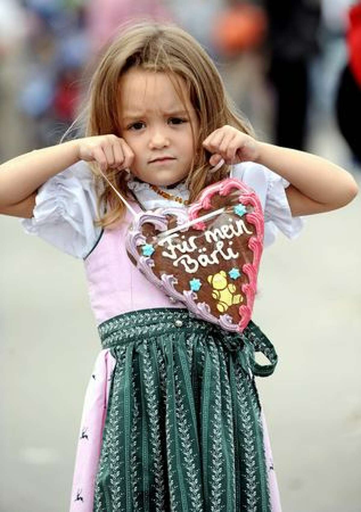 A young girl holds a gingerbread heart during the Oktoberfest beer festival at the