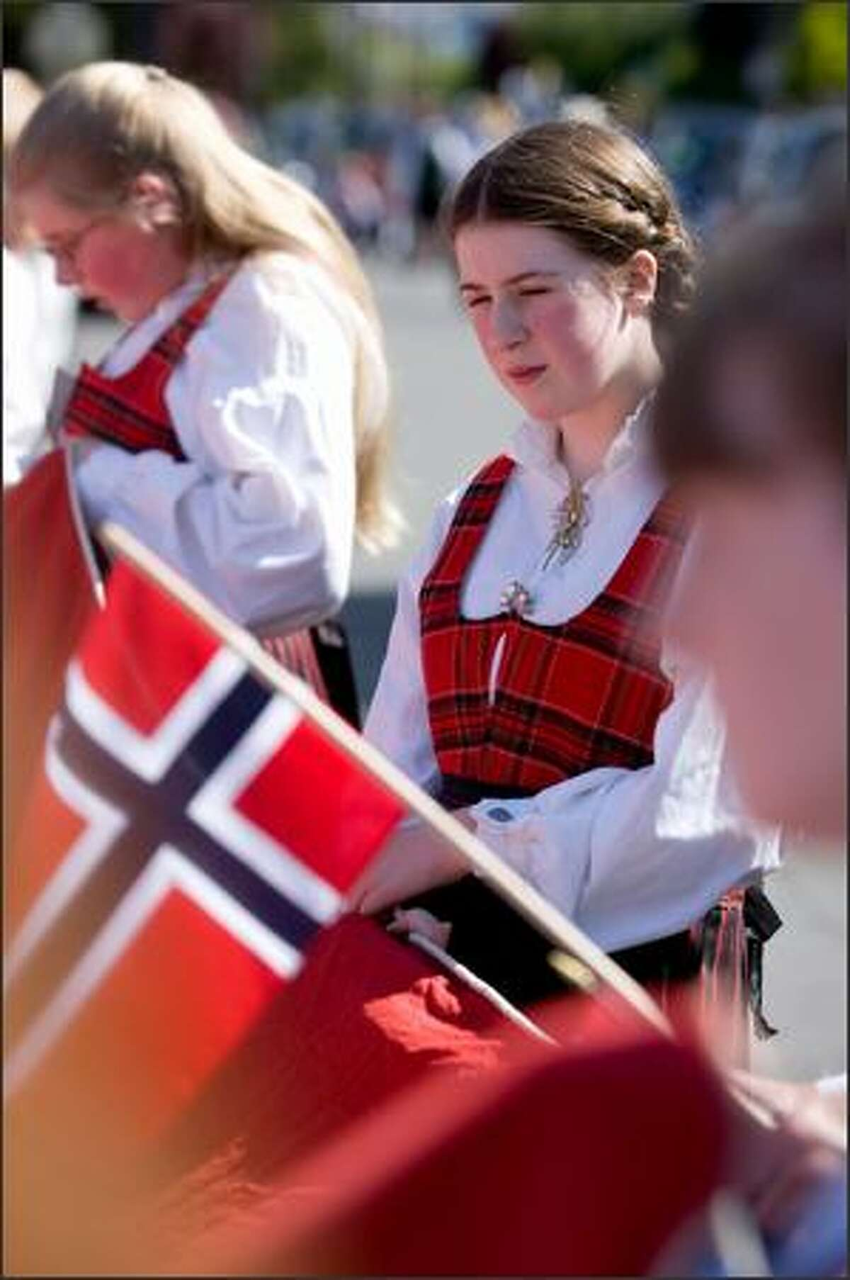 Anna Ripley, 12, relaxes alongside sister Tera Jane, 13, left, before the start of the Norwegian Constitution Day parade in Ballard.