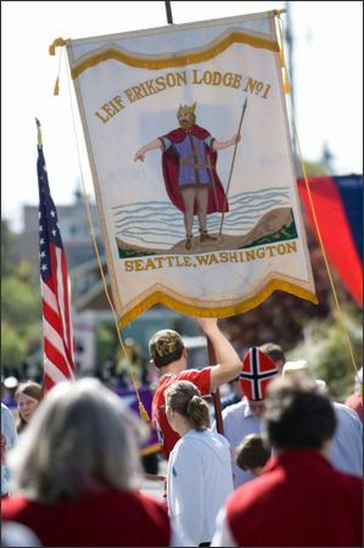 A banner for the Leif Erikson lodge is held up by Court Potter before the start of the Norwegian Constitution Day parade in Ballard.
