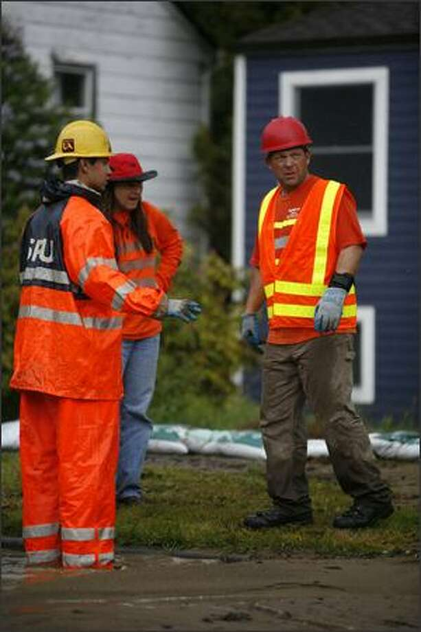 Seattle Public Utility workers survey the scene after a water main burst, flooding homes on Tuesday. Photo: Joshua Trujillo, Seattlepi.com