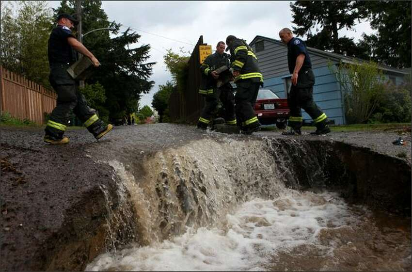 Firefighters use bricks and rocks to divert water from homes after a water main burst on Tuesday in Seattle's Ravenna neighborhood.
