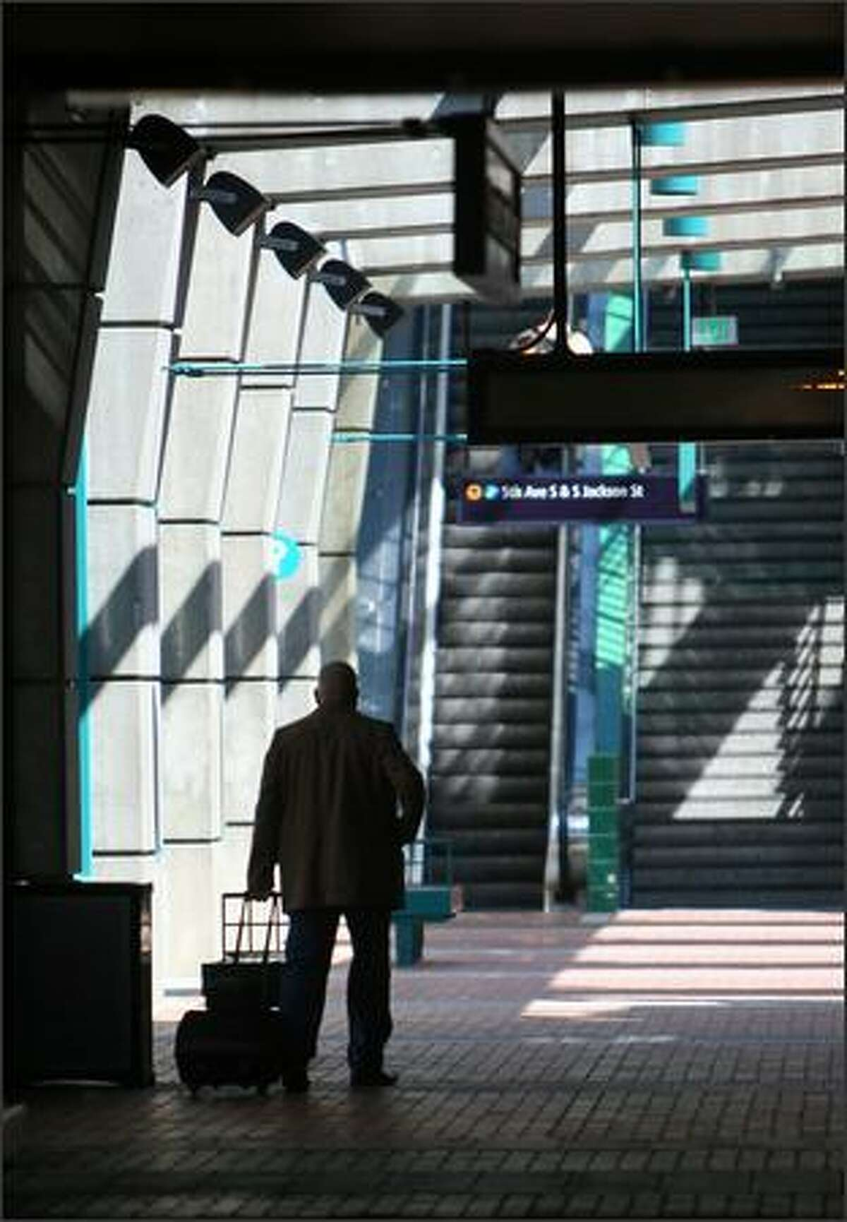A bus passenger walks through a terminal at the Downtown Seattle Transit Tunnel. Sound Transit's Link light-rail trains have started two months of test runs through the tunnel, moving alongside buses.