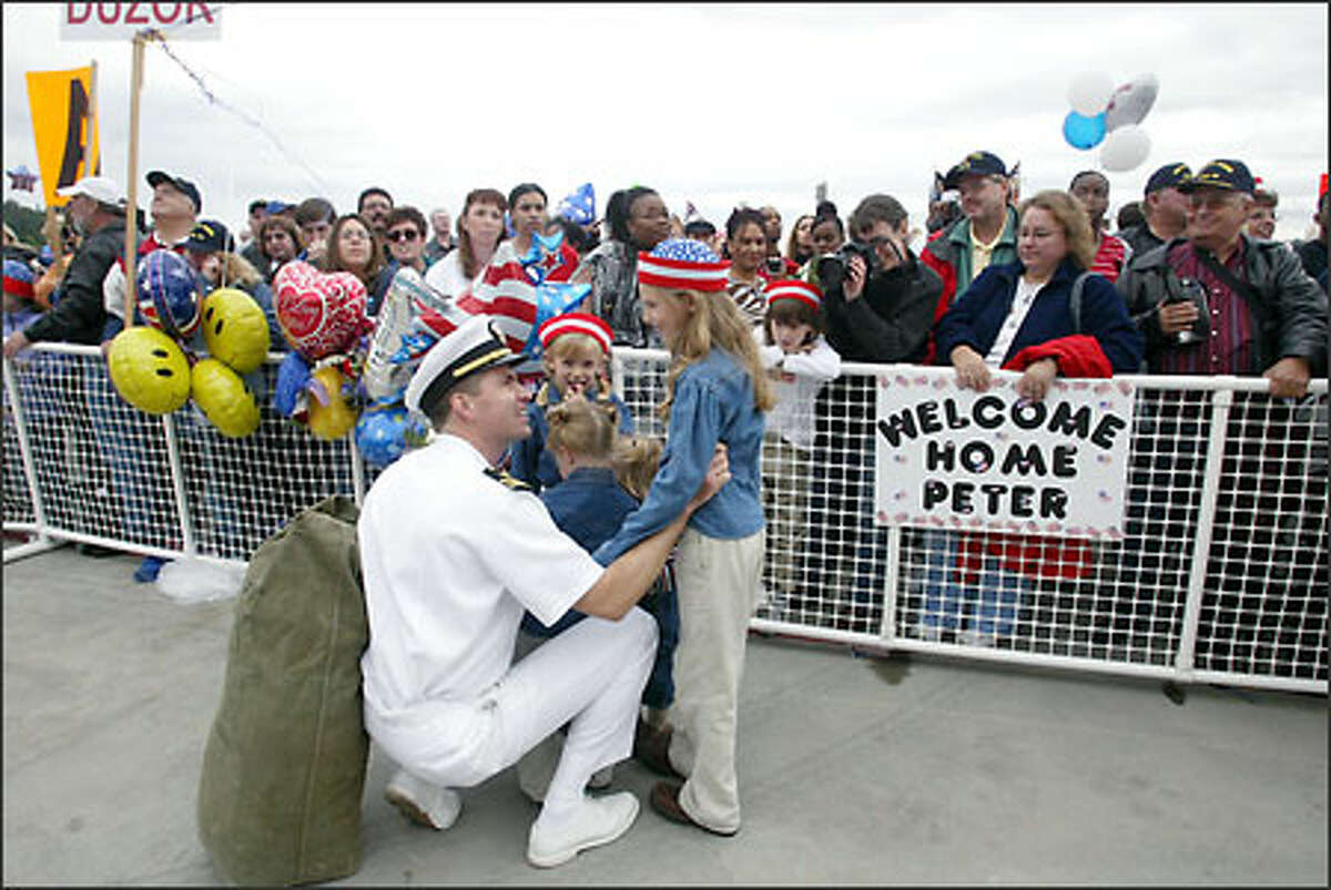 Lt. Cmdr. A.J. Reiss, of Port Orchared, is greeted by his four daughters -- Dasha Reiss, 8 (standing, right); Julia, 5; Emma, 3; and Annie, 2 -- after the USS Carl Vinson returns to Bremerton after eight months at sea.
