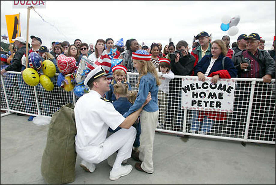 Lt. Cmdr. A.J. Reiss, of Port Orchared, is greeted by his four daughters -- Dasha Reiss, 8 (standing, right); Julia, 5; Emma, 3; and Annie, 2 -- after the USS Carl Vinson returns to Bremerton after eight months at sea. Photo: Karen Ducey, Seattle Post-Intelligencer