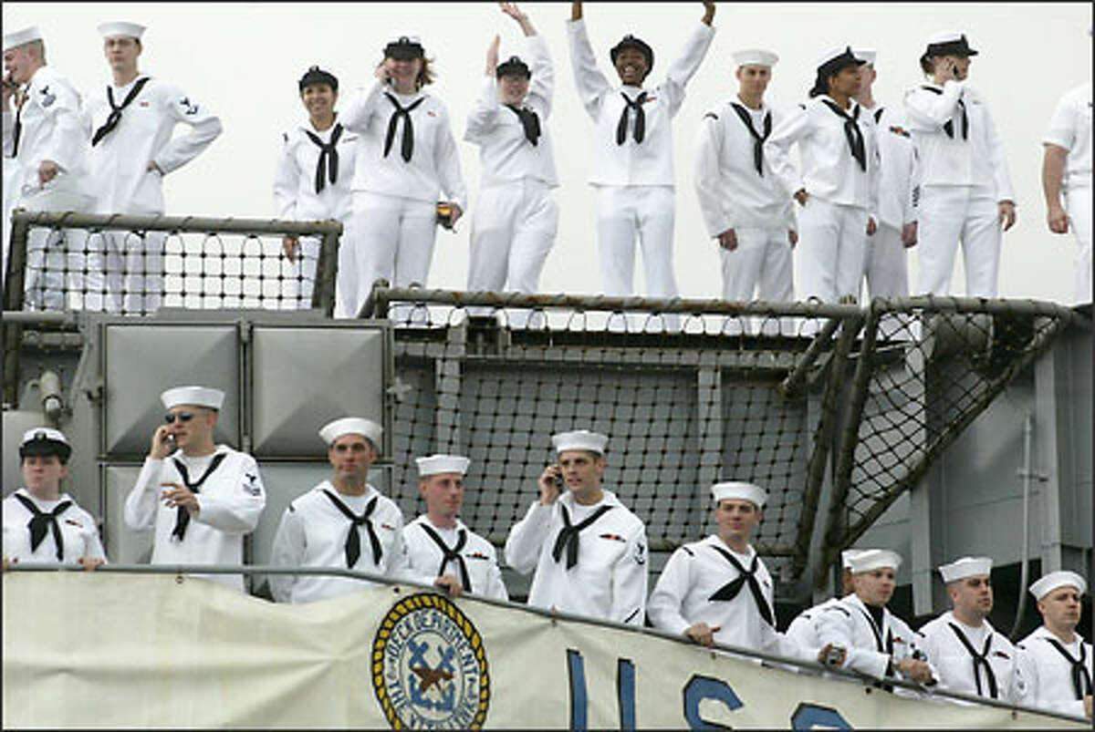 Sailors on board the USS Carl Vinson wave to the crowd upon their return to Bremerton after eight months at sea.
