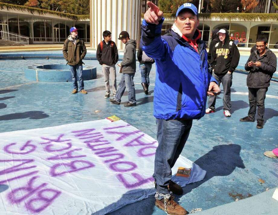 UAlbany student and veteran, Chris Schewe, 41, of Pittstown stands chains to the fountain at UAlbany's main campus in Albany Friday morning March 25, 2011.   (John Carl D'Annibale / Times Union) Photo: John Carl D'Annibale