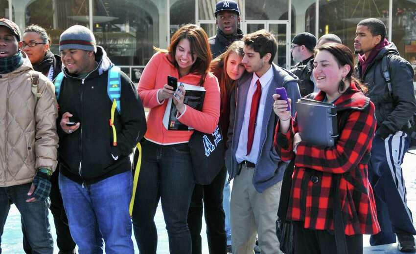 A small group of UAlbany students look on as fellow student and veteran, Chris Schewe, 41, of Pittstown is chained to the fountain at UAlbany's main campus in Albany Friday morning March 25, 2011. (John Carl D'Annibale / Times Union)