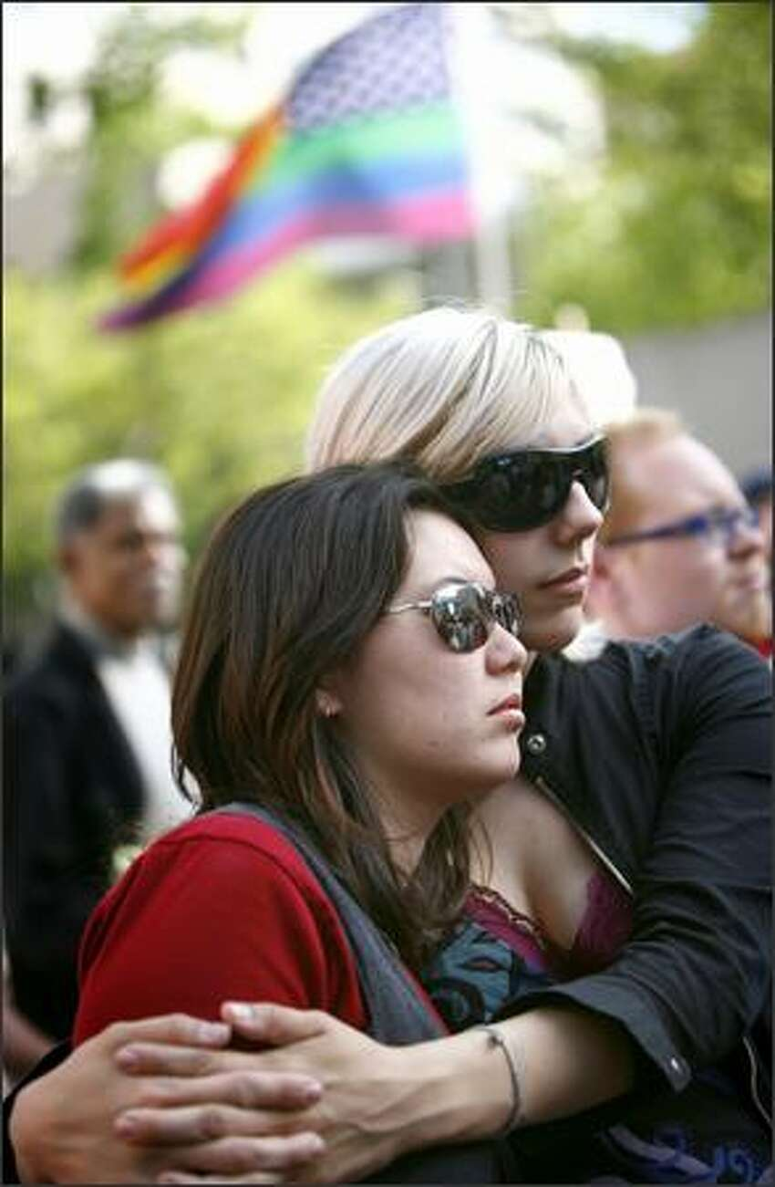 Sarah Hu, left, and her girlfriend Markie Miller listen to a speech during the rally.