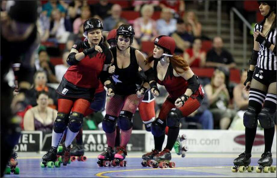 Skaters turn a corner of the track during the Rat City Rollergirls' Season Five Championship Bout! between the Throttle Rockets and Grave Danger at KeyArena in Seattle on Saturday. Photo: Clifford DesPeaux, Seattlepi.com