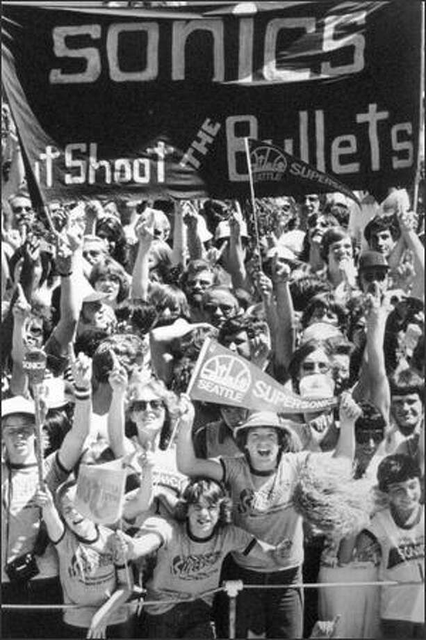 Letting out the biggest Sonic Boom of the season, some 40,000 fans greeted the returning champions at Sea-Tac airport in June of 1979.  Above is part of the cheering throng.  To the right is Billy Huls, 11, of Des Moines, who wore his feelings across his face.  Below, David Russe peeled off part of his 85-pound Wheedle costume to take a break from the heat and hustle of the day. (seattlepi.com file)