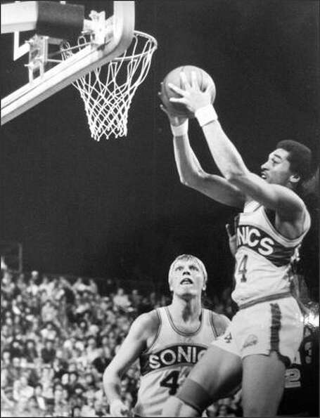 Dennis Johnson (24) of Seattle hauled in a rebound while teammate Jack Sikma looked on during action